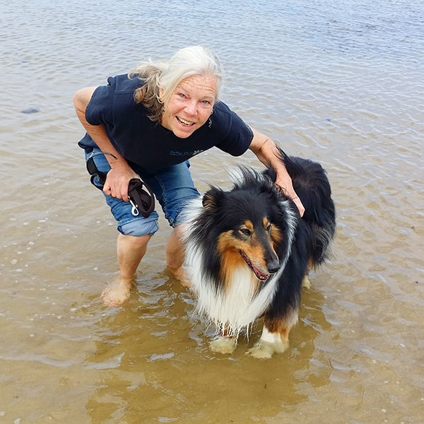 Crosspaws owner Sylvie and Jezz the collie standing in the surf